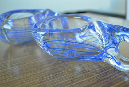 "Two blue and white glass Kuksas on a table with ""Fulbright Finland 70"" carving on them"