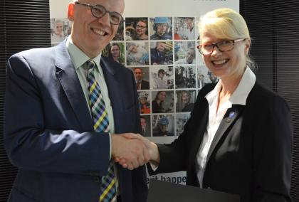 VTT CEO Antti Vasara and Fulbright Finland Foundation CEO Terhi Mölsä smiling and shaking hands in front of VTT poster after signing the agreement