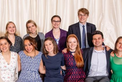 2018-2019 U.S. Fulbright Fellows sitting in two rows and hugging each other, smiling at the camera at the Helsinki City Hall after 2019 Fulbright Award Ceremony