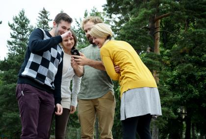Group of American Fulbright Finland grantees looking a phone in front of pine trees