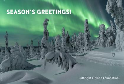 "Green aurora borealis in the background with snowy trees in the front. ""Season's Greetings!"" written on the upper left corner, Fulbright Finland Foundation in the lower right corner. The photo is credited Thomas Kast / Visit Finland."