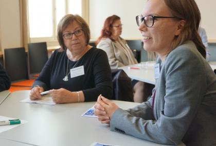 Workshop participants, two women, one of which is talking and other one is listening. They are sitting around a white round table.