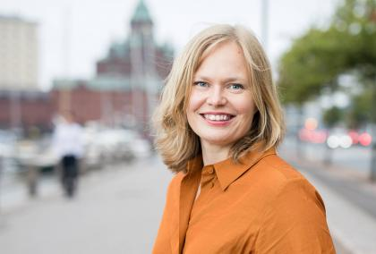 Minister of Science and Culture Hanna Kosonen in a orange dress photographed on a street in Helsinki