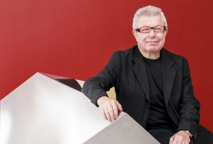 Architect Daniel Libeskind sitting on a geometrical shape with a deep red wall in the background