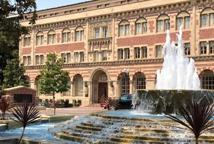 Photo of University of Southern California campus with a university building and water fountain.