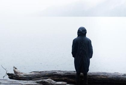 A person wearing dark coat standing by themselves on a shore of a misty lake, looking to the lake and standing their back to the camera.