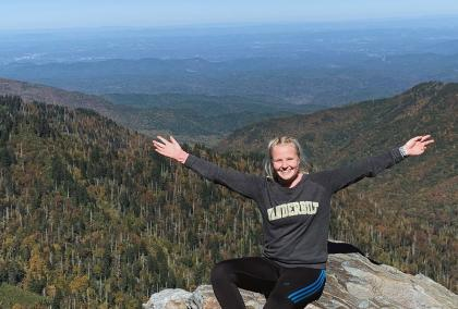 Fulbright Finland grantee Agneetta Moisio sitting on top of a mountain with her arms spread on her side. She is wearing her university's, Vanderbilt University, college shirt and smiling to the camera.