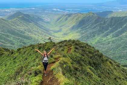 Fulbright Finland Undergraduate grantee Isa Lassinaro standing on a trail on a green mountain in Hawaii