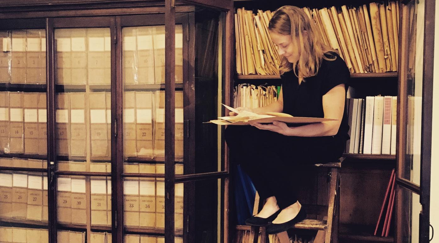 ASLA-Fulbright Graduate Grantee 2016-2017 Petra Kuivala sitting on a ladder in Cuban studies archive room reading a folder