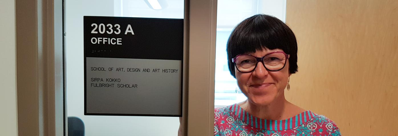"MCPD Sirpa Kokko smiling next to a sign saying ""Sirpa Kokko, School of Art, Design, and Art History, Fulbright Scholar"""