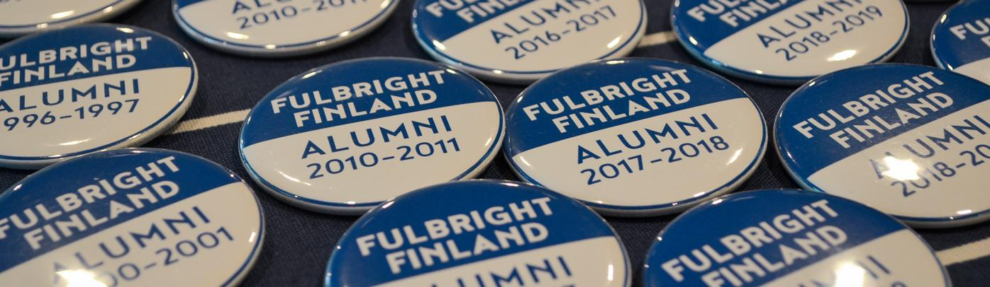 Blue and white buttons saying Fulbright Finland Alumni and a year on a table