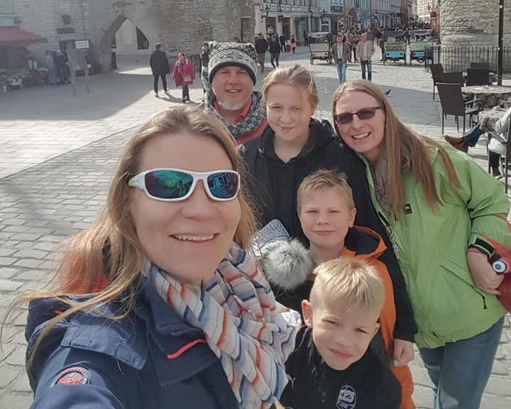 Bickford family with their friend taking a selfie, smiling to the camera. They are on a town square and the weather is sunny.