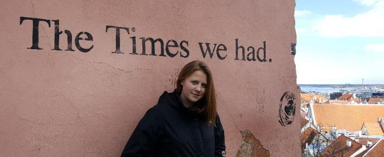"A teenage girl standing in front of a pink wall that has ""The Times We Had"" written on it. Tallin's old town is visible on the right."