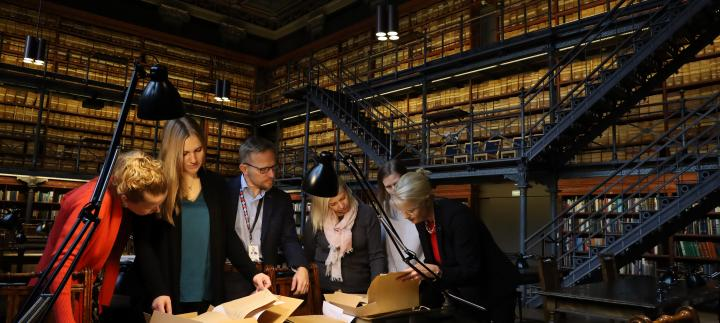 Fulbright Finland team members with Administrative Director Immo Aakkula going through the Foundation's archives in the reading room at the National Archives of Finland