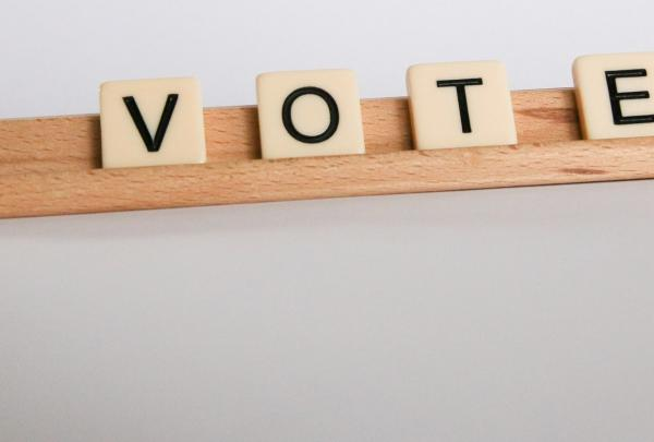 Scrabble tiles spelling out the word VOTE on a wooden Scrabble tile holder