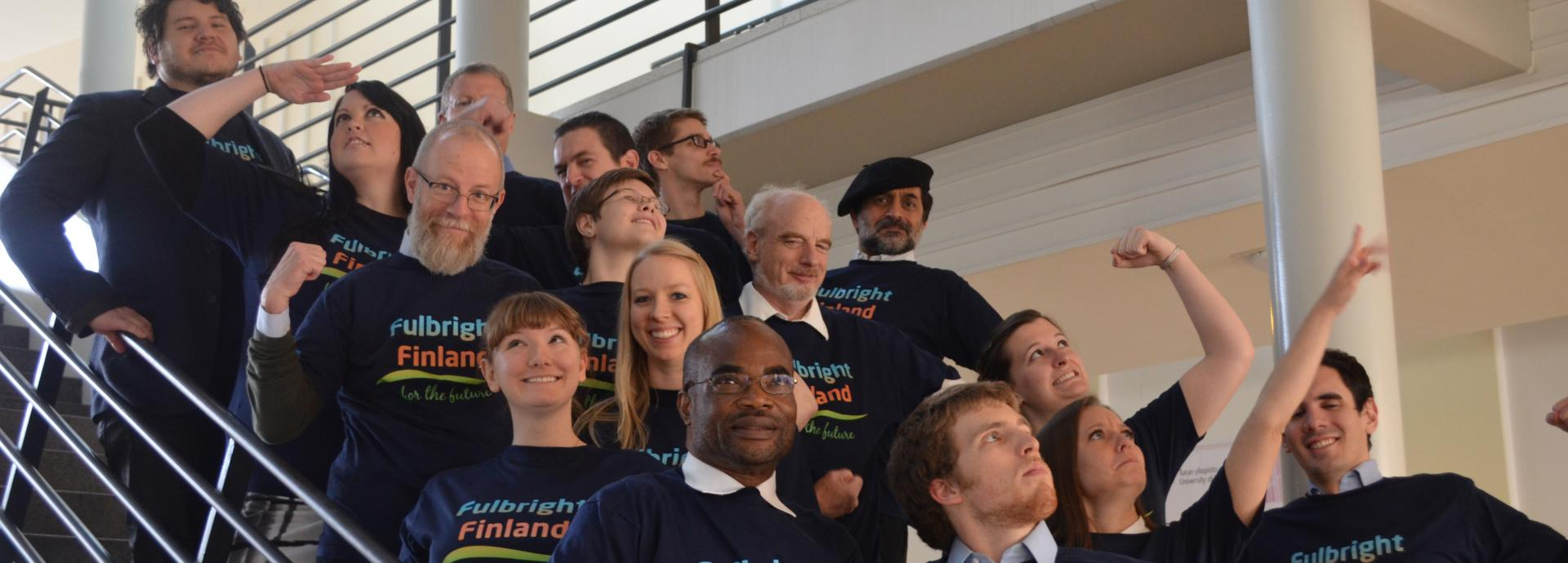 Group of American Fulbrighters wearing Fulbright Finland t-shirts on a staircase making superhero-like moves