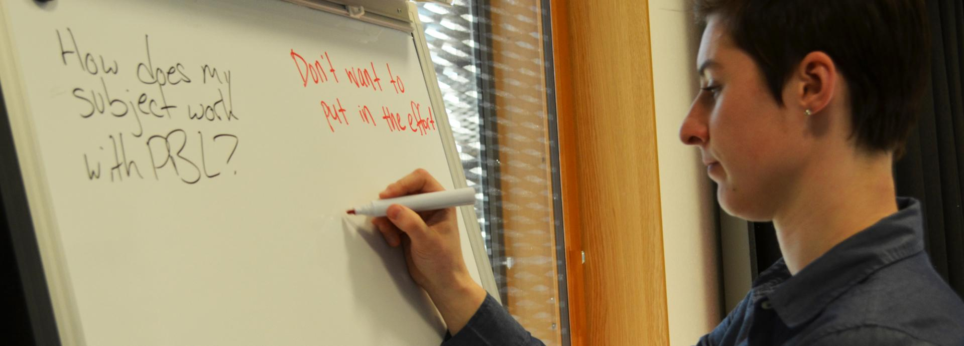 A student writing with a red marker on a white board with questions on it