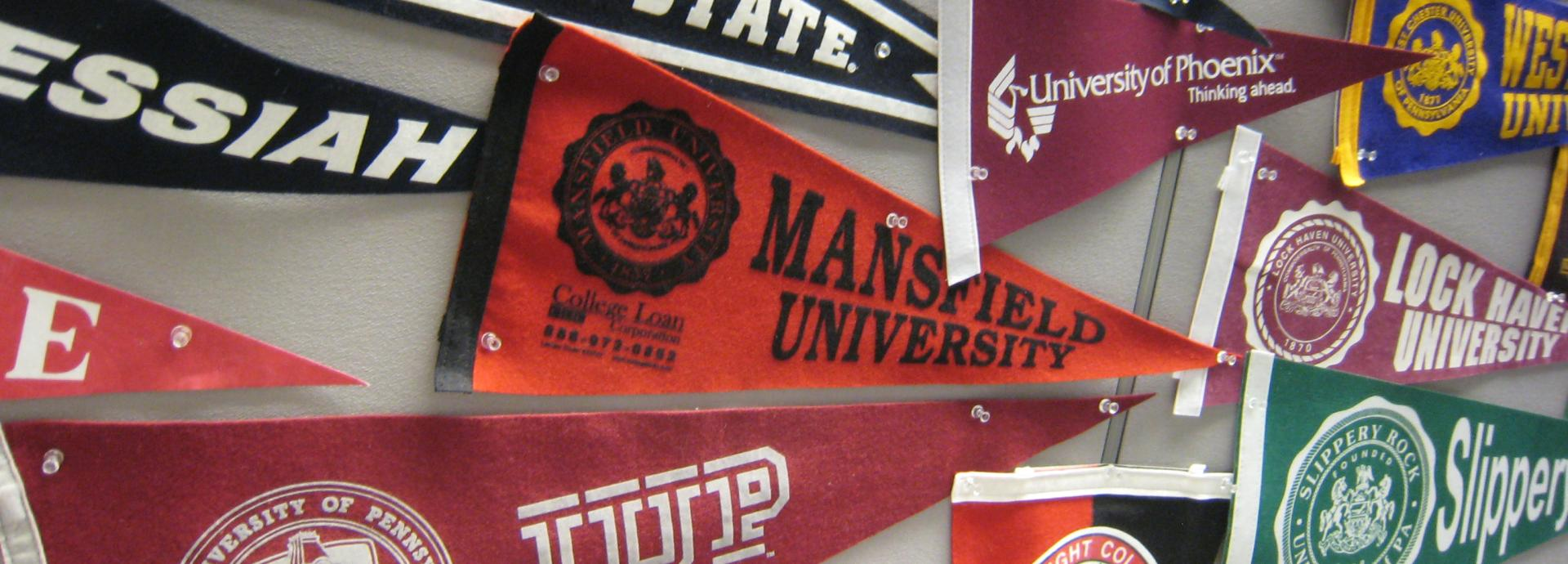 Many different university flags pinned on a wall