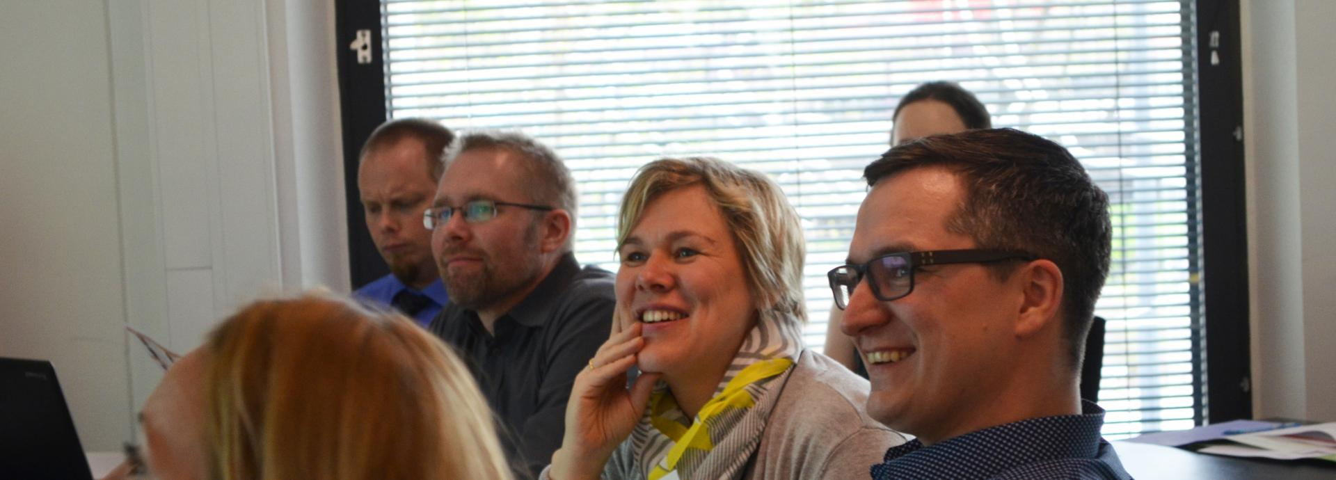 Three men and one woman looking at something during orientation and laughing.