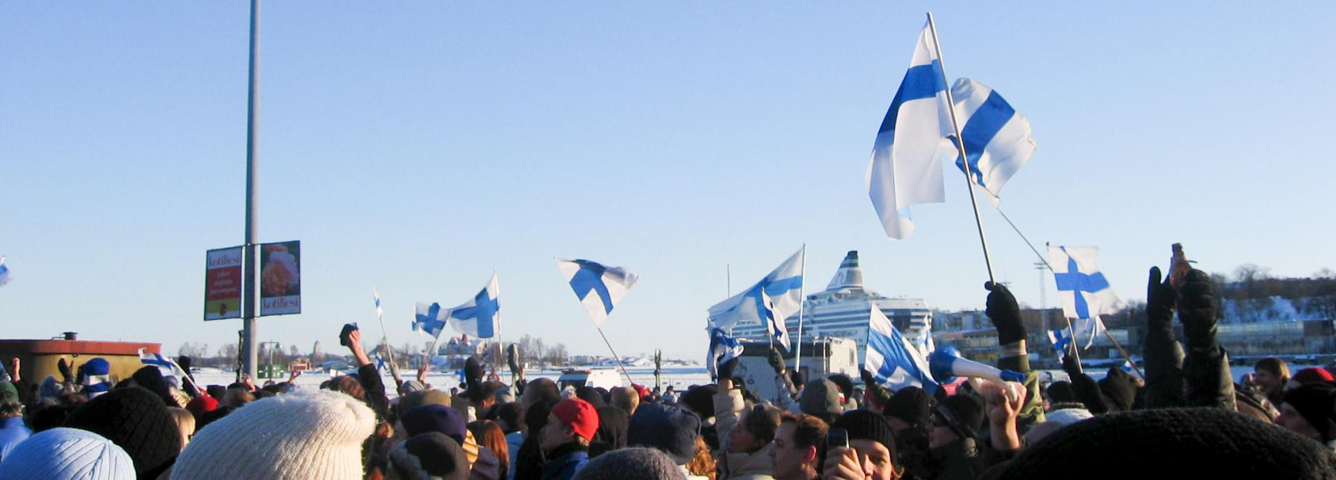 A big crowd of people at the Helsinki Market Square during winter waving Finnish flags