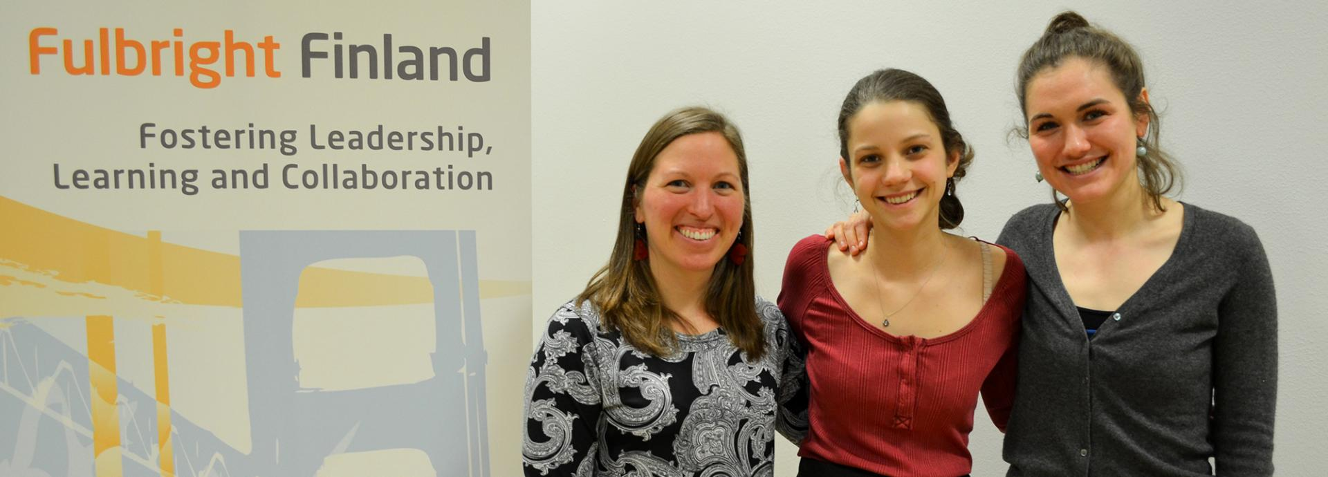 2017 Roth Endowment Award winners smiling next to Fulbright Finland roll-up