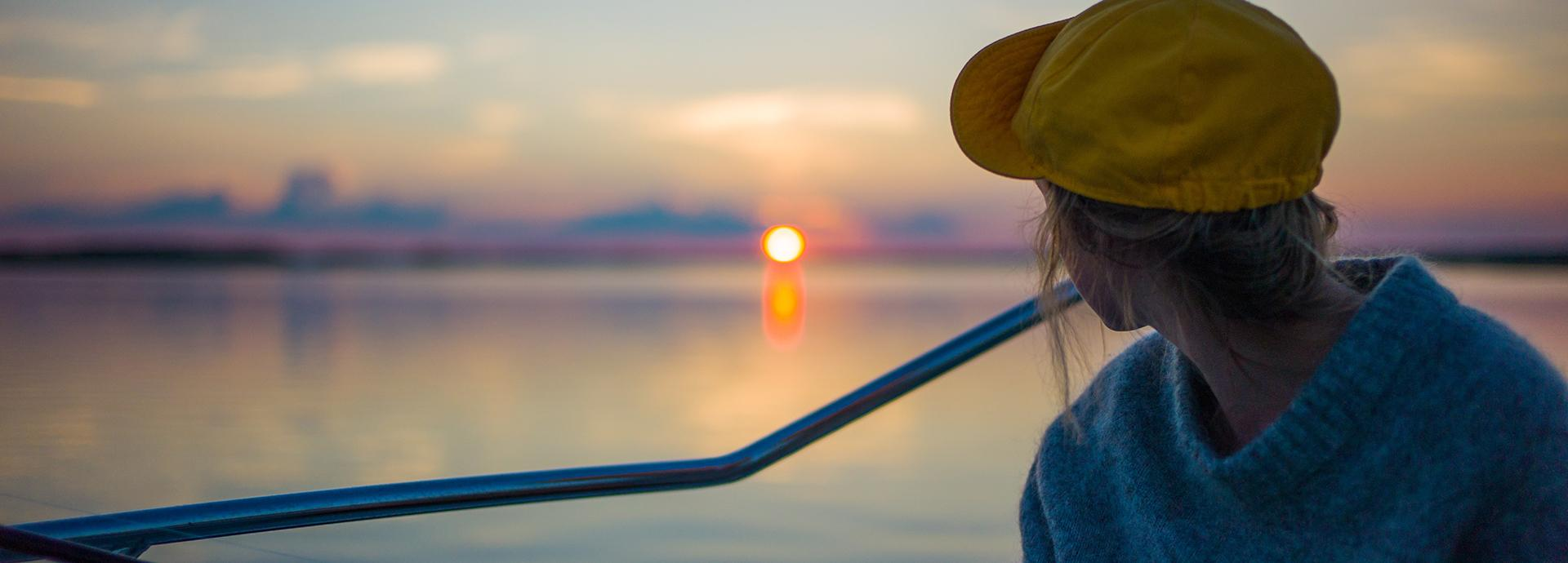 A person wearing a yellow cap sitting a boat looking at a sun setting behind a lake