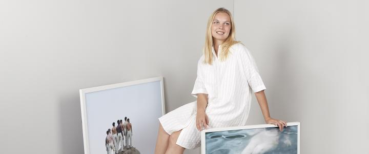 Lotta Lemetti sitting and smiling among her photos. She is wearing a white dress and is in a white room.