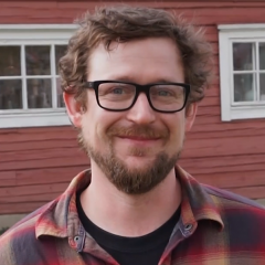 2018-2019 U.S. Fulbright Fellow Jonathan Capps smiling in front of a red wooden house
