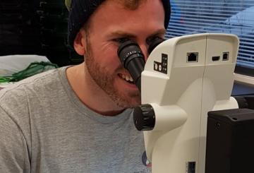A man looking at a sample through a microscope