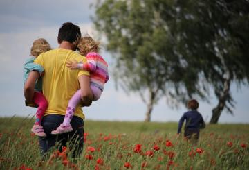 A man carrying two girls on a field of flowers