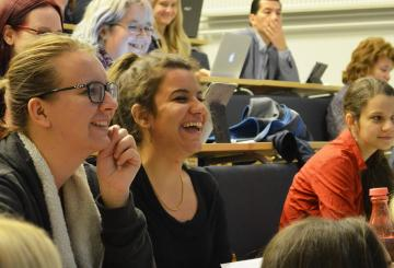 Students laughing in a full lecture hall
