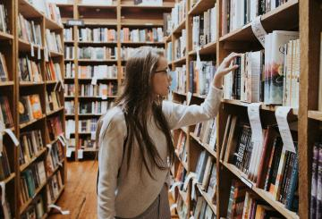 A girl searching books in a library.